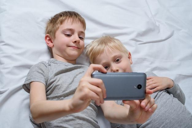 Zwei jungen liegen mit einem smartphone im bett. gadget freizeit Premium Fotos