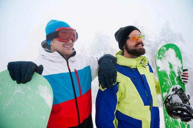 Zwei jungs mit snowboards in der winterpause Kostenlose Fotos