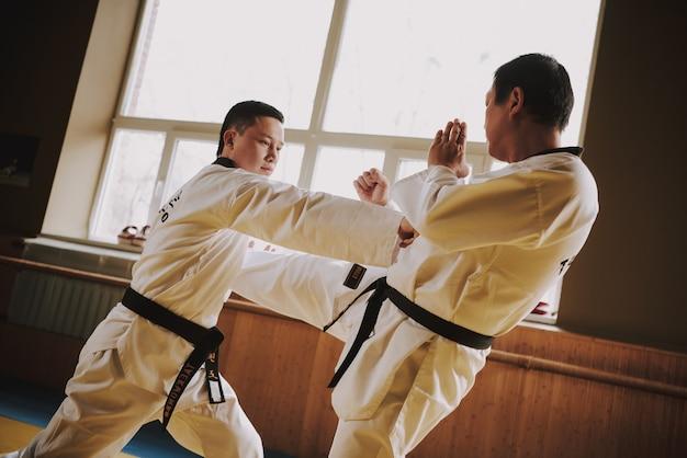 Zwei kampfkunststudenten im weißen sparring zusammen. Premium Fotos