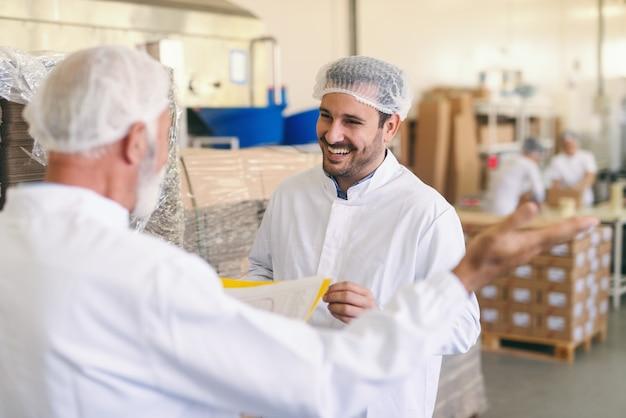 Zwei kaukasische arbeiter im schutzanzug sprechen und lächeln, während sie in der lebensmittelfabrik stehen. Premium Fotos