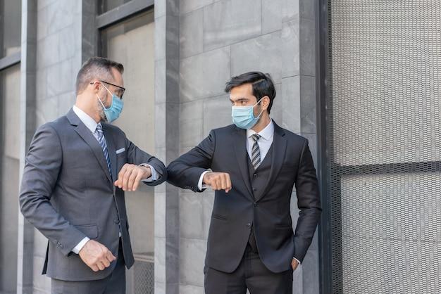 Zwei kaukasische geschäftsleute tragen eine medizinische maskenbegrüßung mit stoßenden ellbogen während der covid-19-epidemie des coronavirus auf der straße Premium Fotos