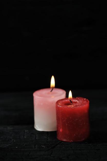 Zwei kerzen mit beleuchtetem feuer auf schwarzem hintergrund Premium Fotos