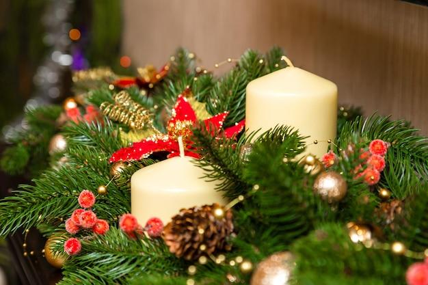 Zwei kerzen mit dekoration des weihnachtsbaumes Premium Fotos