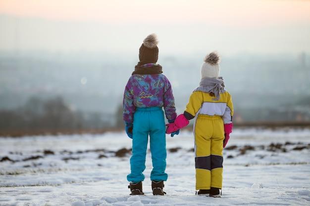 Zwei kinder bruder und schwester stehen draußen auf schneebedeckten winterfeld händchen haltend. Premium Fotos