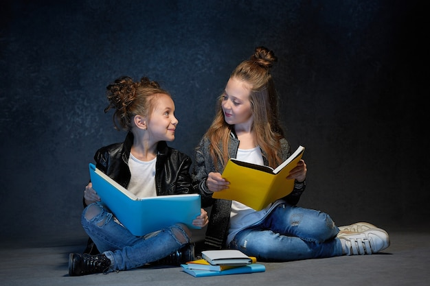 Zwei kinder, die das buch im grauen studio lesen Kostenlose Fotos