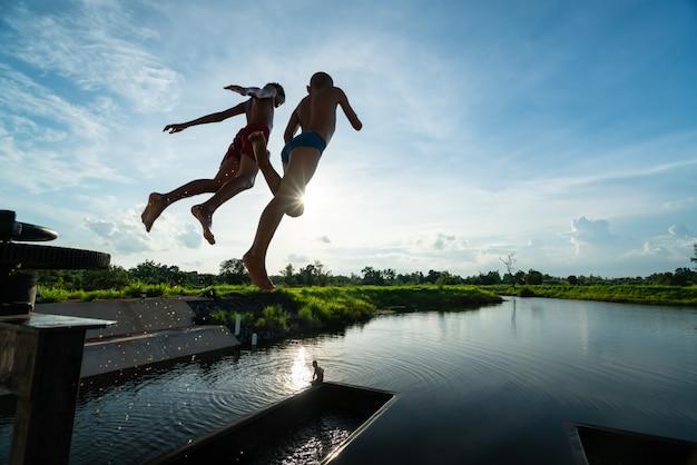 Zwei kinder in der luft beim springen in see mit schönem sonnenstrahl Premium Fotos