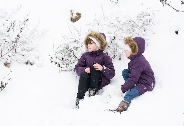 Zwei kinder in lila jacken sitzen in der nähe von schneebedeckten büschen Premium Fotos
