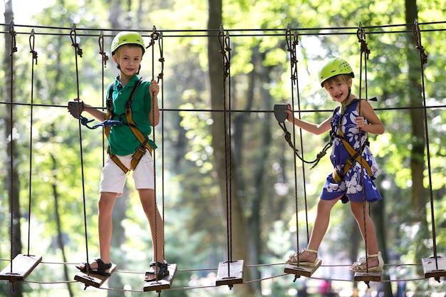 Zwei kinder, junge und mädchen im schutzgurt und schutzhelme beim klettern auf seilbahn. Premium Fotos