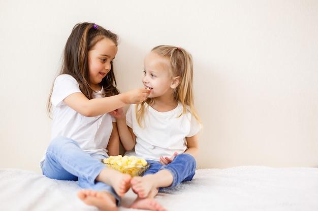 Zwei kinder mit popcorn gegen den weißen hintergrund Premium Fotos