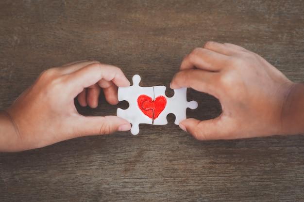 Zwei kinderhände, die paarpuzzlestück mit gezogenem rotem herzen verbinden Premium Fotos
