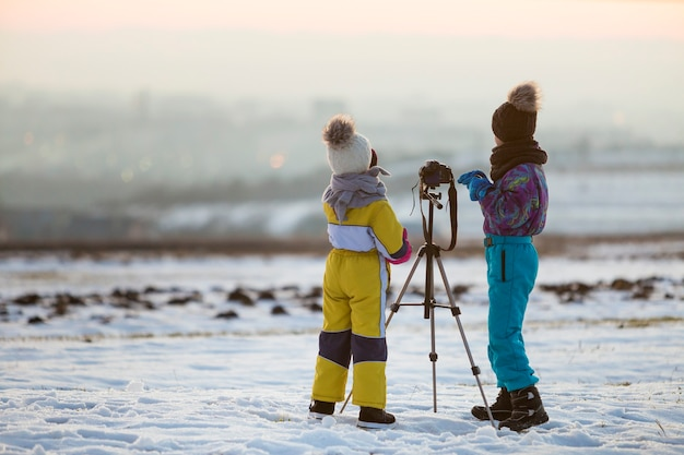 Zwei kinderjunge und -mädchen, die spaß draußen im winter spielen mit fotokamera Premium Fotos