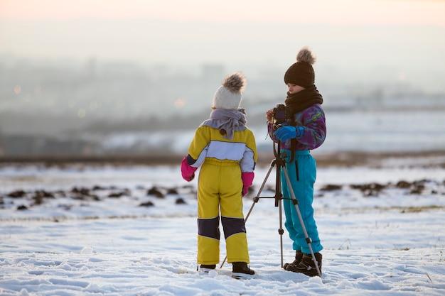 Zwei kinderjungen und -mädchen, die spaß draußen im winter haben Premium Fotos