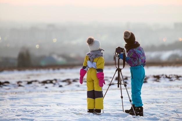 Zwei kinderjungen und -mädchen, die spaß draußen im winter spielen mit fotokamera auf einem stativ auf schneebedecktem feld spielen. Premium Fotos