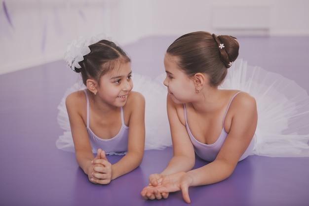 Zwei kleine ballerinas, die nach tanzstunde sprechen Premium Fotos
