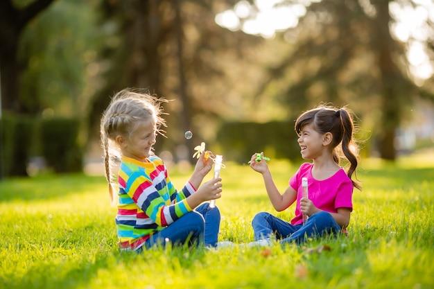 Zwei kleine blonde mädchen und ein brünetter sommer sitzen