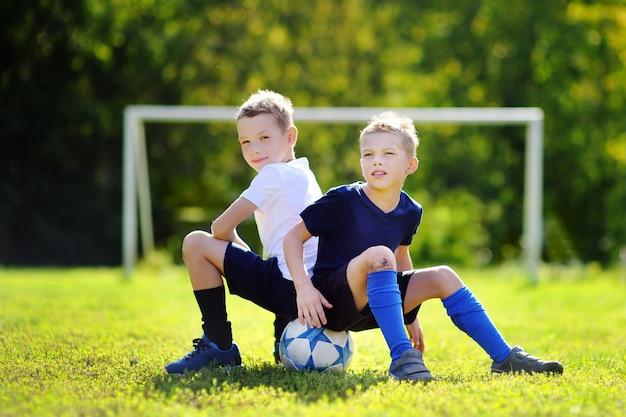 Zwei kleine brüder, die spaß haben, ein fußballspiel am sonnigen sommertag zu spielen Premium Fotos