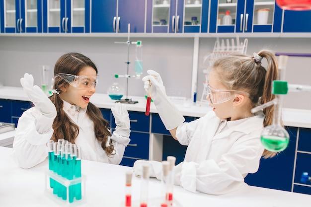 Zwei kleine kinder im laborkittel lernen chemie im schullabor. junge wissenschaftler in schutzbrillen machen experimente im labor oder im chemikalienschrank. zutaten für experimente untersuchen. Premium Fotos