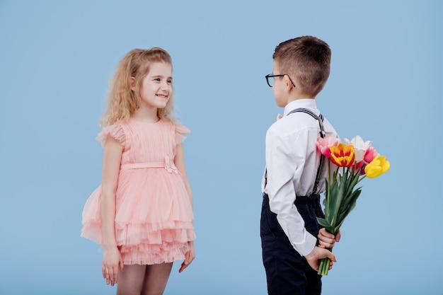 Zwei kleine kinderjunge mit blumen und mädchen im rosa kleid, lokalisiert auf blauer wand Premium Fotos