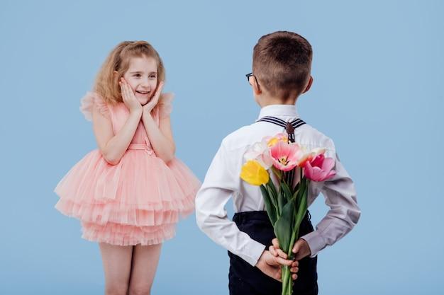 Zwei kleine kinderjunge mit blumen und überraschtem mädchen im rosa kleid, lokalisiert auf blauer wand Premium Fotos