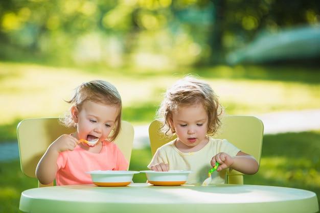 Zwei kleine mädchen, die an einem tisch sitzen und zusammen gegen grünen rasen essen Kostenlose Fotos