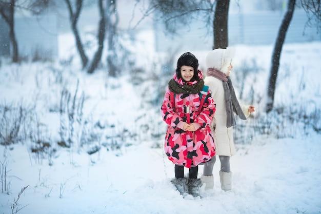 Zwei kleine mädchen, die draußen während der starken schneefälle spielen. Premium Fotos