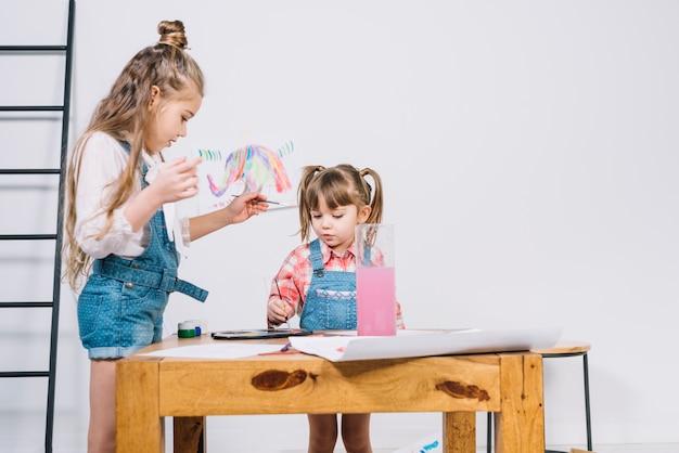 Zwei kleine mädchen, die mit aquarell auf papier malen Kostenlose Fotos