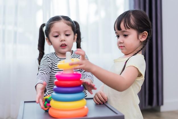 Zwei kleine mädchen, die zusammen kleine spielzeugbälle im haus spielen. bildung und glückseligkeit Premium Fotos