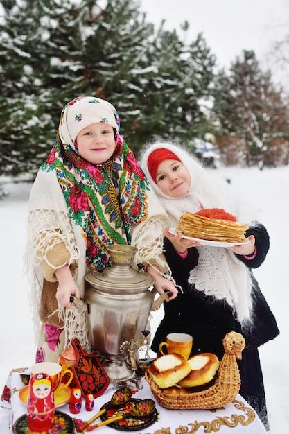 Zwei kleine mädchen in pelzmänteln und tüchern im russischen stil Premium Fotos