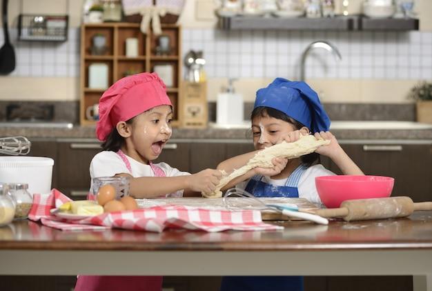 Zwei kleine mädchen machen pizza Premium Fotos