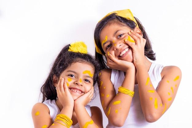 Zwei kleine mädchen, mit ihrem gesicht gemalt, um den gelben tag zu feiern Premium Fotos