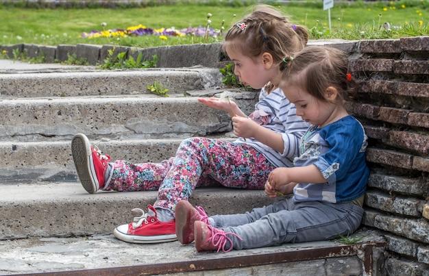 Zwei kleine mädchen sitzen auf den stufen draußen, das konzept, sich auszuruhen, kinder Kostenlose Fotos