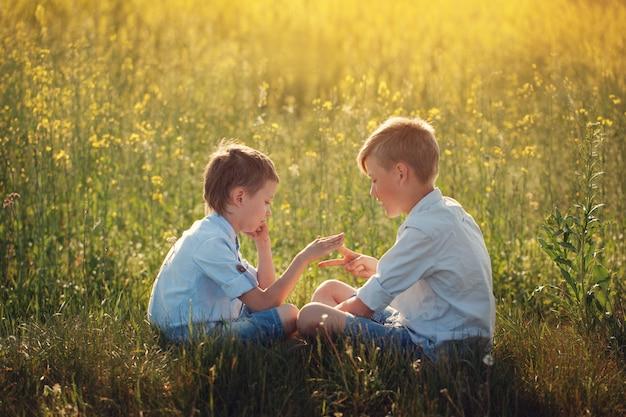 Zwei kleine spielende freunde - stein, schere, papierspiel am sommertag. Premium Fotos