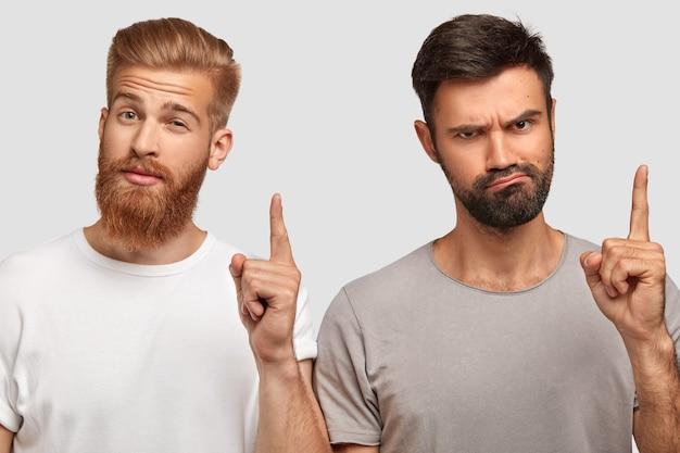Zwei kluge schüler mit ernstem gesichtsausdruck, die die vorderfinger heben und eine gute idee für die projektarbeit haben Kostenlose Fotos