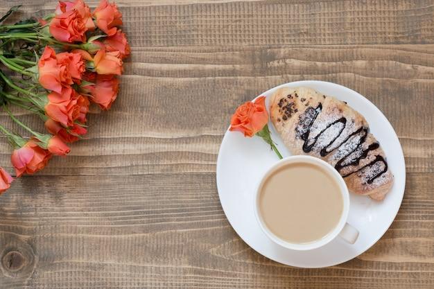 Zwei köstliche frisch gebackene schokoladenhörnchen und -tasse kaffee auf hölzernem brett. ansicht von oben. frühstückskonzept. kopieren sie platz. Premium Fotos