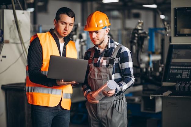Zwei kollegen in einer fabrik Kostenlose Fotos