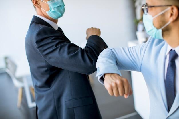 Zwei kollegen vermeiden einen handschlag, wenn sie sich im büro treffen, und grüßen mit stoßenden ellbogen Premium Fotos