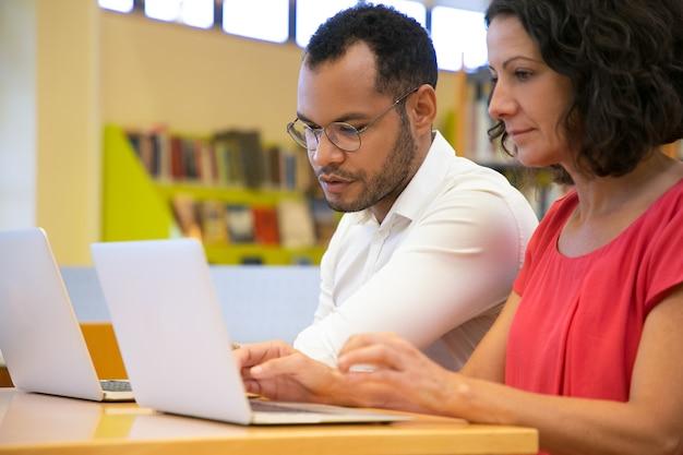 Zwei konzentrierte studenten, die laptop an der bibliothek sprechen und betrachten Kostenlose Fotos