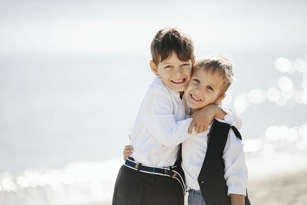 Zwei lächelnde brüder umarmen sich in der nähe des meeres und schauen geradeaus Kostenlose Fotos