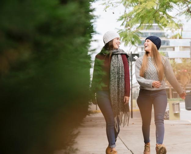 Zwei lächelnde frauen, die in den park gehen Kostenlose Fotos