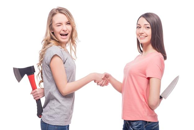 Zwei lächelnde frauen, die vertraulich stehen und messer halten. Premium Fotos