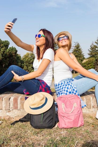 Zwei lächelnde freundinnen, welche die sonnenbrille nehmen selfie am handy tragen Kostenlose Fotos