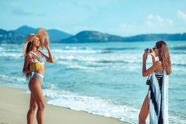 Zwei lächelnde junge freundinnen, die bikinis tragen und das kokosnusscocktailnehmen während des bräunens auf einem tropischen sandigen strand während der ferien Premium Fotos