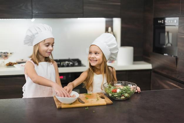 Zwei lächelnde mädchen, die lebensmittel in der küche zubereiten Kostenlose Fotos