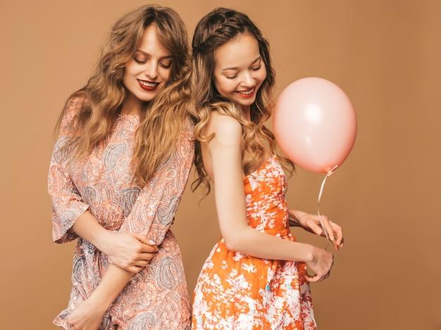 Zwei lächelnde schöne frauen in den sommerkleidern. mädchen posieren. modelle mit bunten luftballons. spaß haben, bereit zum feiergeburtstag oder zur urlaubsparty Kostenlose Fotos