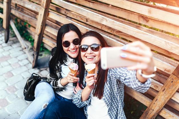 Zwei lange haare brunettemädchen, die das selfie im freien machen Premium Fotos