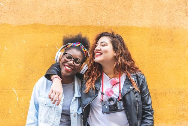 Zwei lateinische jugendlichen, die zusammen über einer gelben wand stehen. Premium Fotos