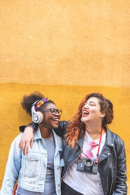 Zwei lateinische jugendlichen, die zusammen über einer gelben wand stehen Premium Fotos