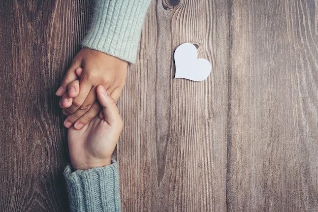 Zwei leute, die hände zusammen mit liebe und wärme auf holztisch halten Kostenlose Fotos