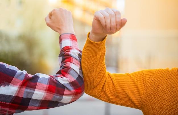 Zwei leute stoßen an die ellbogen Premium Fotos