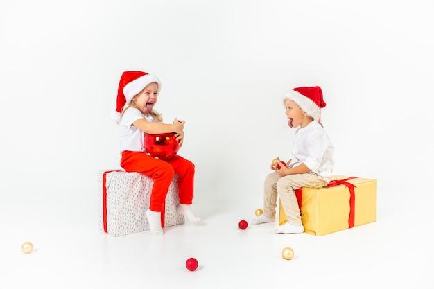 Zwei lustige kleinkinder in sankt-hut, der auf geschenkboxen sitzt. isoliert auf weißem hintergrund weihnachten und neujahr konzept. Premium Fotos